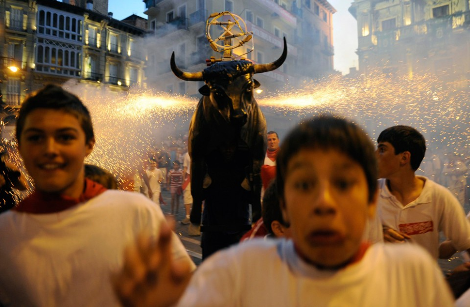 Young-revellers-run-from-the-Fire-Bull-a-man-carrying-a-metal-structure-loaded-with-fireworks-at-the-San-Fermin-festival-in-Pamplona-Spain-on-July-12-2009.-REUTERSEloy-Alonso-960x628